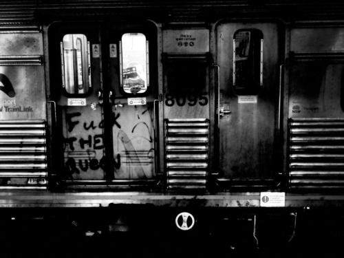 Black and white picture of train carriage with graffiti 'fuck the queen'.