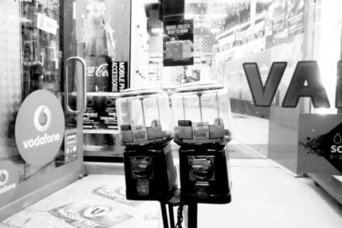 Chew and Bubble. Black and white photograph of two bubblegum machines outside a convenience store on Oxford street Sydney.