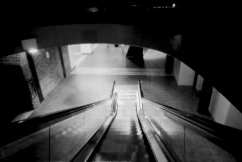 Down into Light. Black and white picture of escalator at Sydney's Central Station.