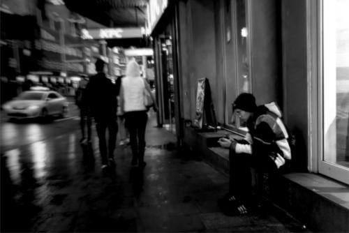 Elsewhere. Black and white picture of young person lost in their phone on a busy Sydney street.