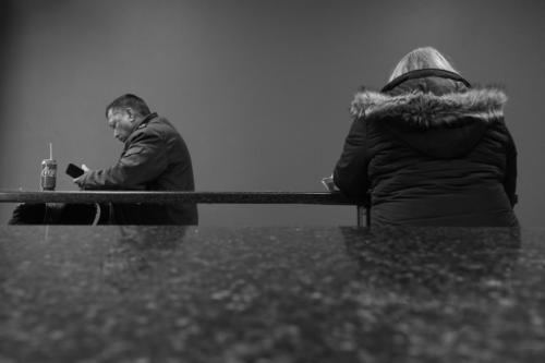 Black and white photograph of a man and a woman at a hamburger joint on a Saturday afternoon. A study on social isolation.