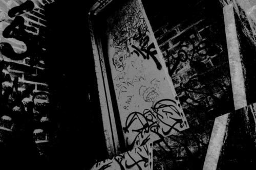 Black and white photograph of tags and graffiti on door in back alley in Katoomba.