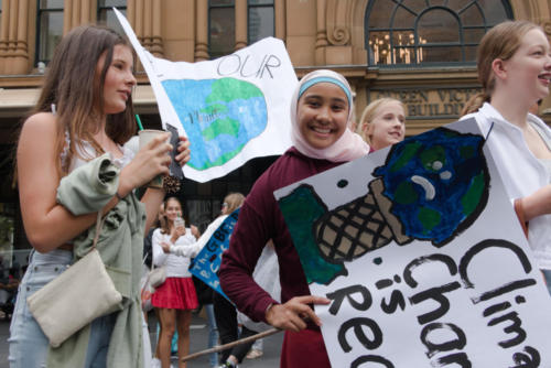 Smiling young woman in Higab with climate action banner.