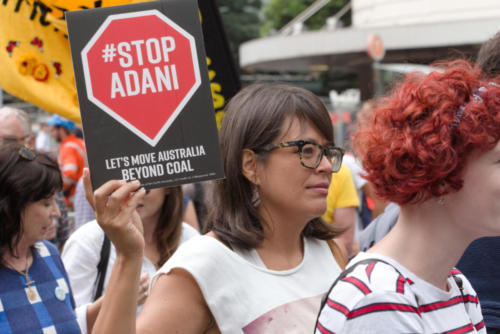 "Young woman with 'Stop Adani"" banner."