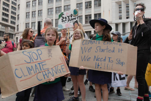 Two young girls with 'Stop Climate Change' banners.