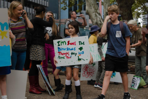 "Little girl with sign ""The Dinosaurs thought they had time as well""."