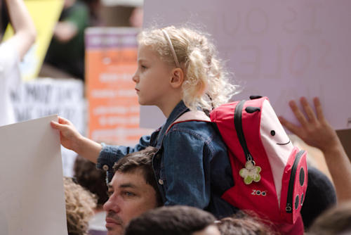 Young blond girl with school bag and banner sitting on a man's shoulders.