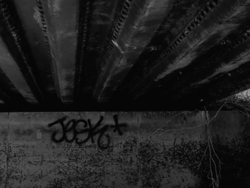Black and white image of tag 'JESK' under bridge over abandoned water canal.