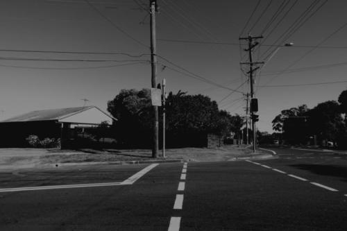 Macquarie Road Crossing. Black and white photograph of a road intersection typical of aspiring-class neighbourhoods in Sydney.