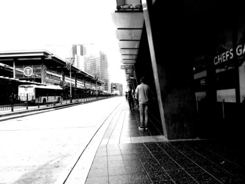 Black and white high-contrast photograph of man standing immobile on the footpath near Parramatta station bus stop. Sydney Australia.