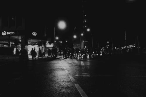 Metro Night. Black and white photograph of home bound people crossing an intersection near Central Station Sydney with Woolworths 'Metro' market on corner.