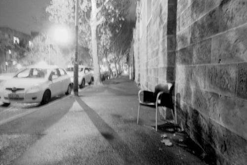 No Oisies. Black and white picture of empty chair against a stone wall close to the 'Wall' in Sydney.