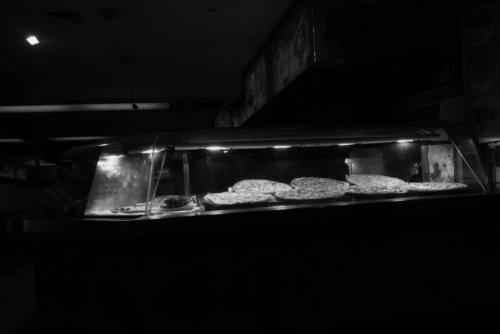 Oxford Pizza.Black and white photograph of a pizza display case on Oxford street. Sydney.