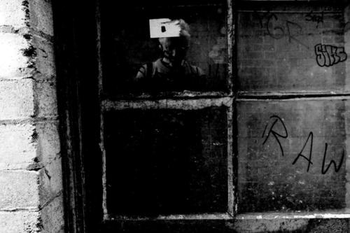 Black and white picture of old window with tags and self-portrait.