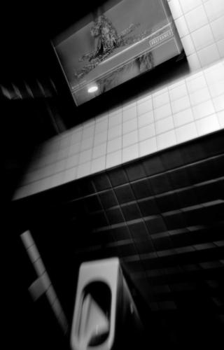 Black and white picture of television screen and railway station public urinal.