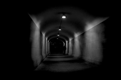 Sadness and Joy. Black and white picture of man walking at night through pedestrian tunnel near Central Station, Sydney.