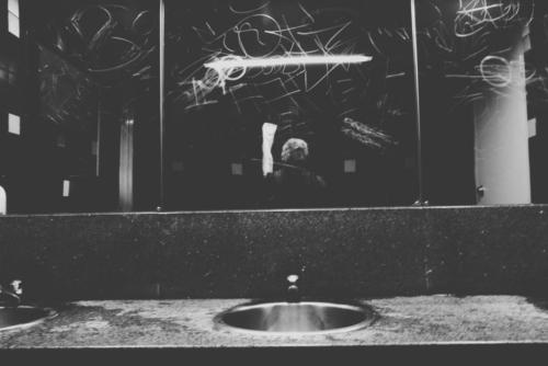 Monochrome picture taken at a public washbasin with tags scratched into mirror and reflection of photographer.