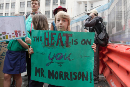 "Little boy holding a banner ""The heat is on you Mr. Morrison!'"